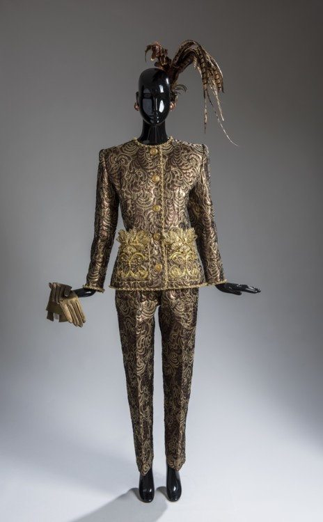 Вечерний ансамбль из парчи с рельефным узором, состоящий из жакета и брюк, расшитых золотыми галунами, серебряными листьями из металла и жемчугом, зима 1990