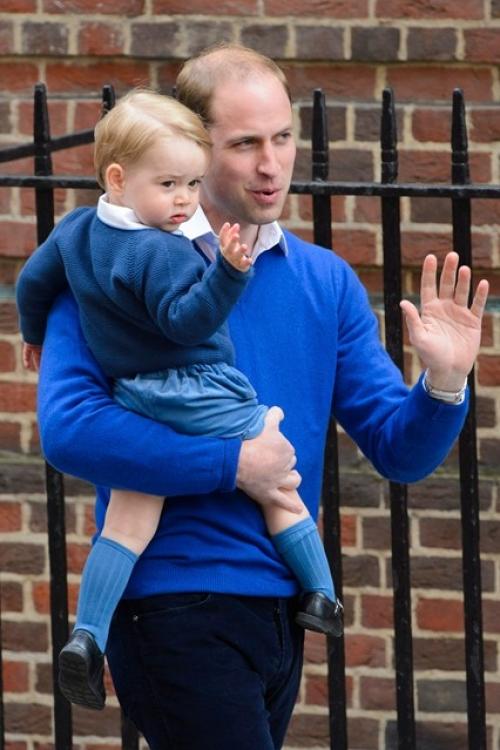 Принц Георг и его отец в соответствующих синих джемперах, встречая Кейт Миддлтон из роддома с малышкой Шарлоттой, приветствуют толпу фотографов