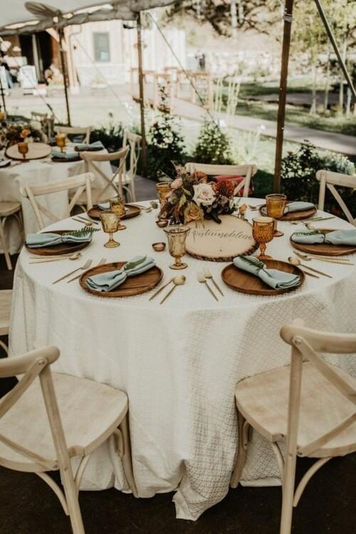 Простое украшение свадебных столов деревянными элементами и цветами. фото