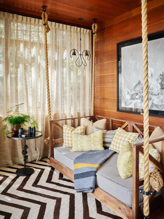 Застекленная терраса. Подвесная кровать дизайна Роберта Бакли. На стене — рисунок Итана Мерроу. На полу — ковер Krimsa