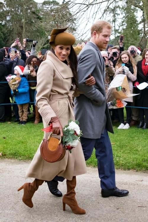 Меган Маркл (пальто Sentaler, сумка Chloé, капелюх Philip Treacy) і принц Гаррі, 25 грудня 2017 р.