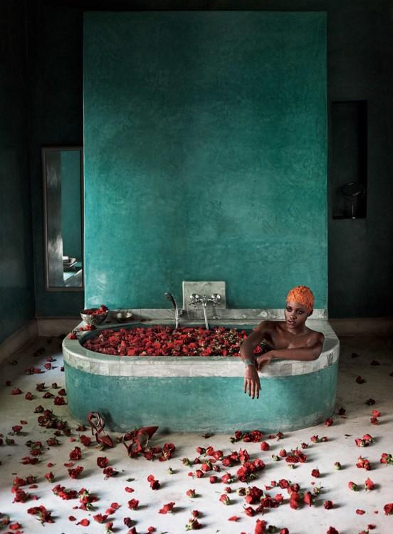Люпита Нионго окунается в ванну с красных роз в марокканском отеле El Fenn. Фото: Микаэль Дженссон, Vogue, 2014