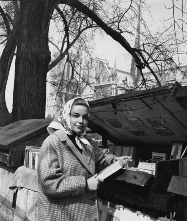 Симона Синьйоре купує книжки поблизу Нотр-Дама де Парі