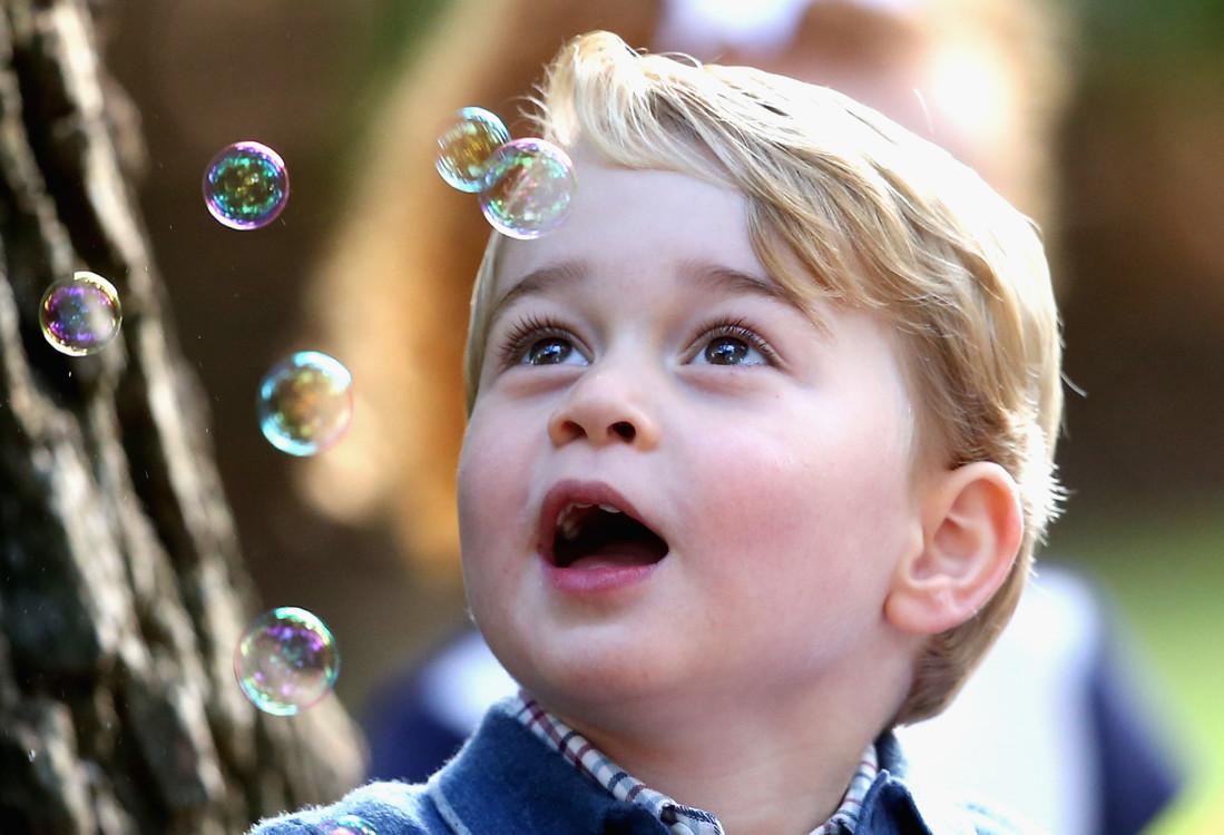 Принц Георг любуется мыльными пузырями на детской вечеринке с семьями военных во время тура по Канаде