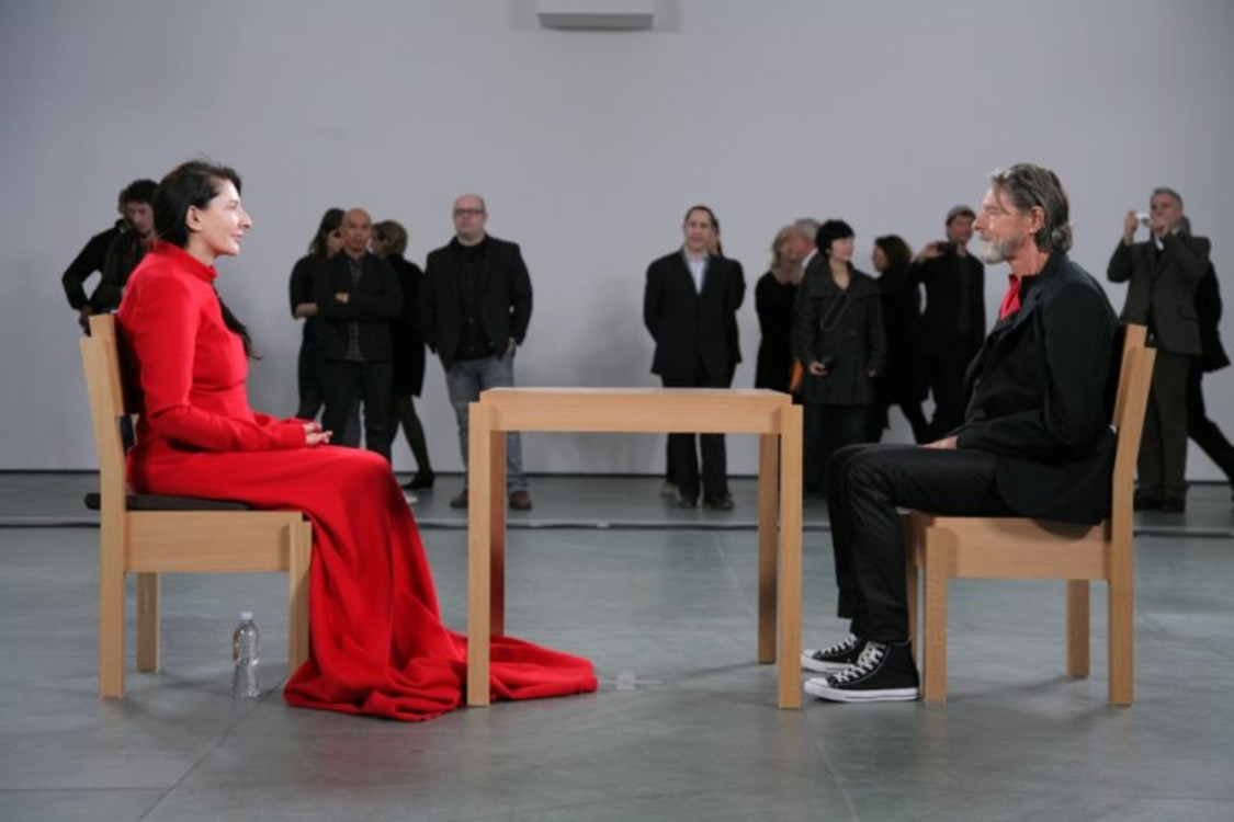 """Перформанс """"В присутствии художника"""". Абрамович в течение трех месяцев в рабочие часы молча сидит за столом в музее и позволяет каждому сесть напротив и посмотреть на нее."""