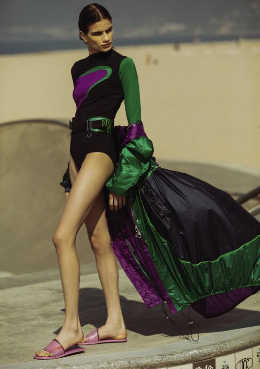 Нейлоновый тренч, комбинезон из вискозы, кожаный пояс, все – Versace; резиновые шлепанцы, Prada