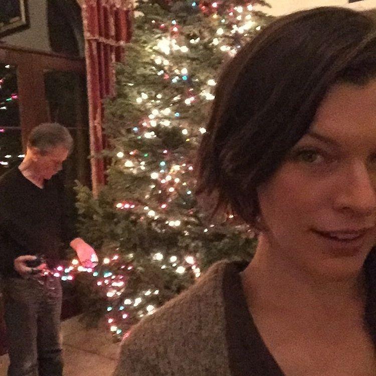 """Милла Йовович рассказывает: """"Готовлюсь к Рождеству всей семьей. Папа позади меня помогает мне с иллюминацией"""""""