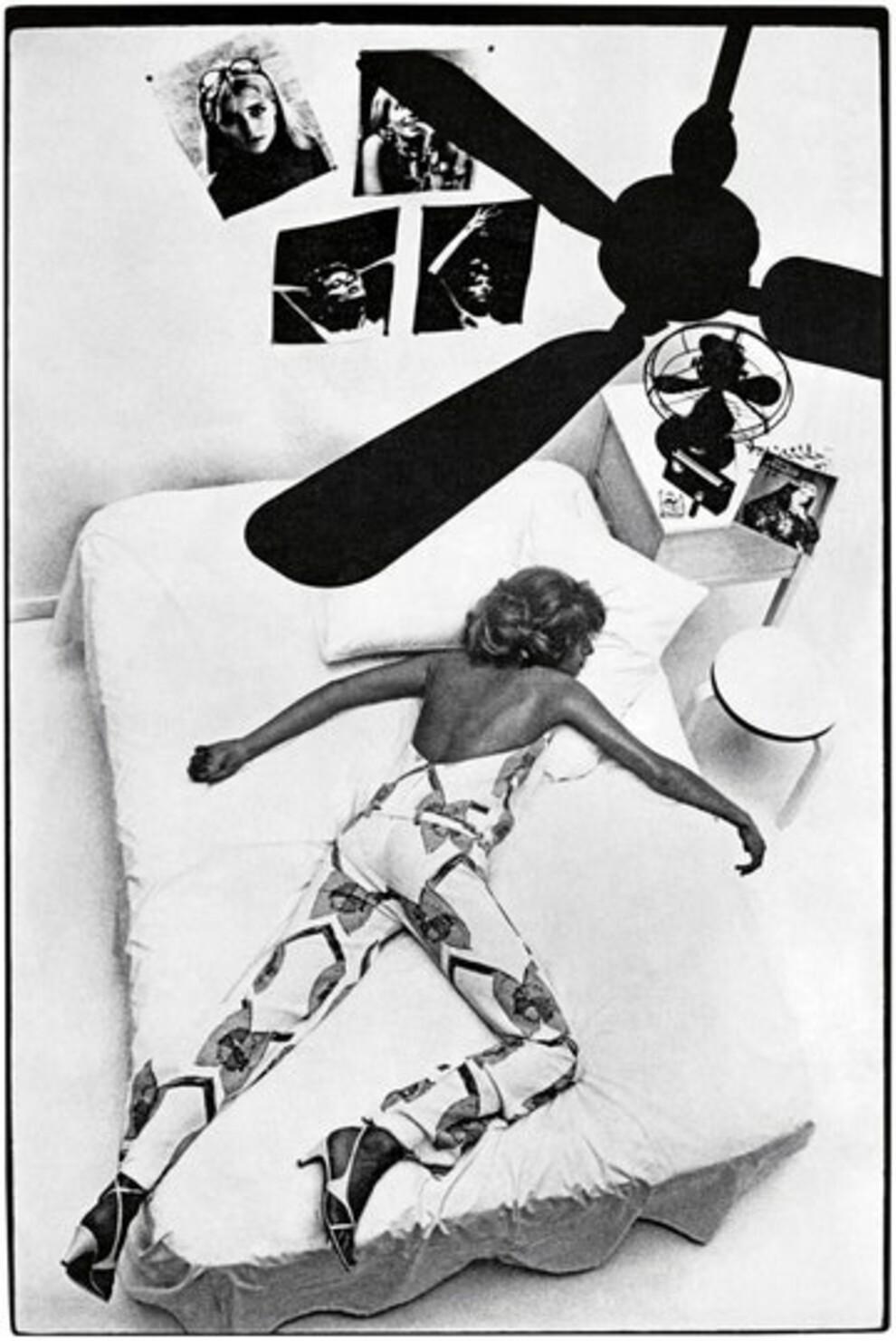Модель лежит на кровати по диагонали в ярком комбинезоне и белых босоножках с перемычками.