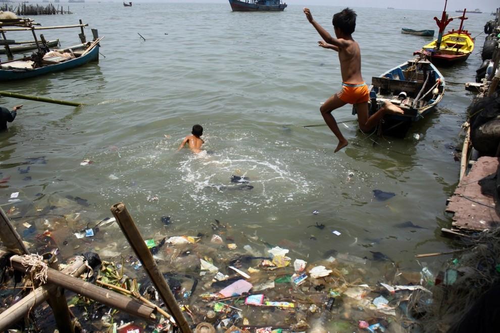 Дети играют в грязной воде в Джакарте.