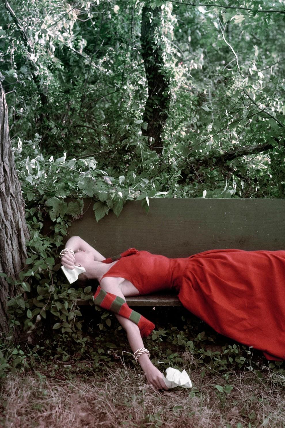 Модель лежит на скамейке в красном длинном платье с салфетками в руках.