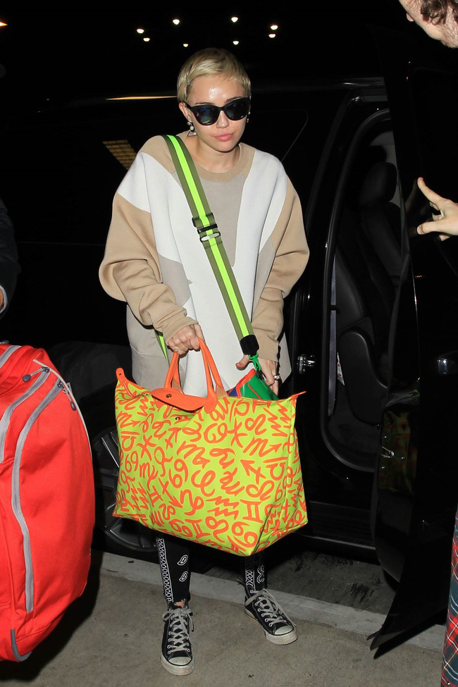 Miley Cyrus with her Longchamp Jeremy Scott limited-edition Le Pliage bag with zodiac signs