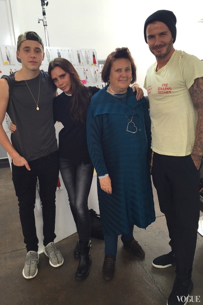 Suzy with David, Victoria and Brooklyn Beckham with images from the spring summer 2016 collection in the background