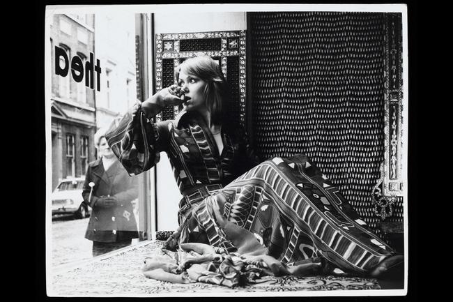 A model in the window of Thea Porter's shop. She wears a silk-chiffon dress with the Samawa carpet print by Sandra Munro. Greek Street, Soho, about 1970