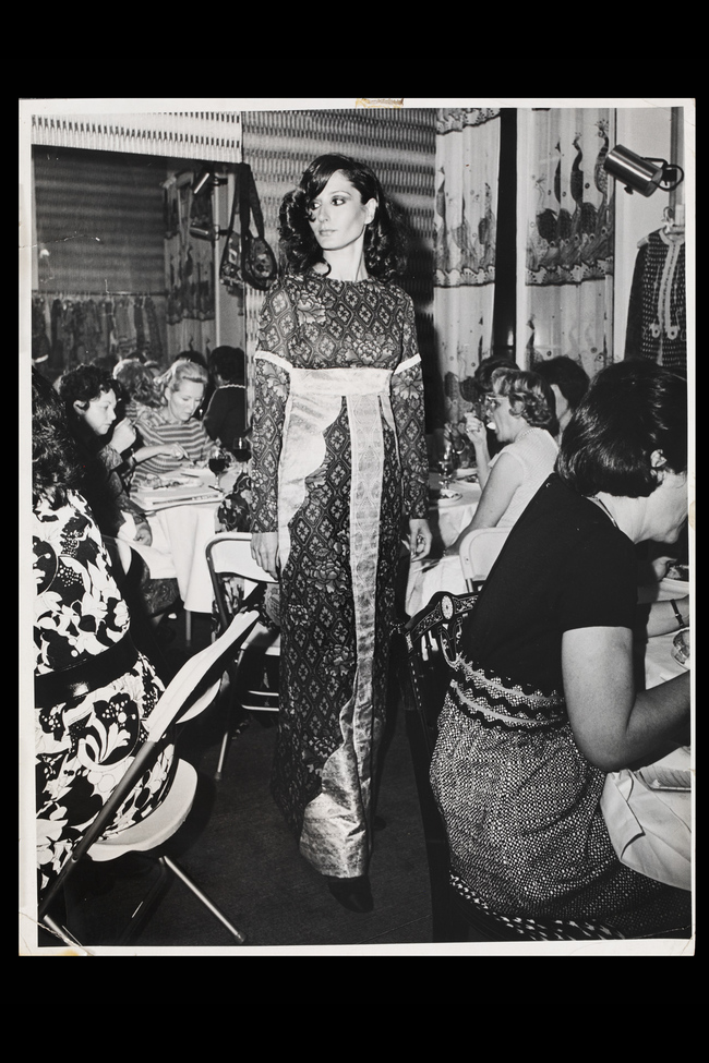 A model wearing a printed silk dress with brocade panels at the press lunch for the New York opening, July 1971