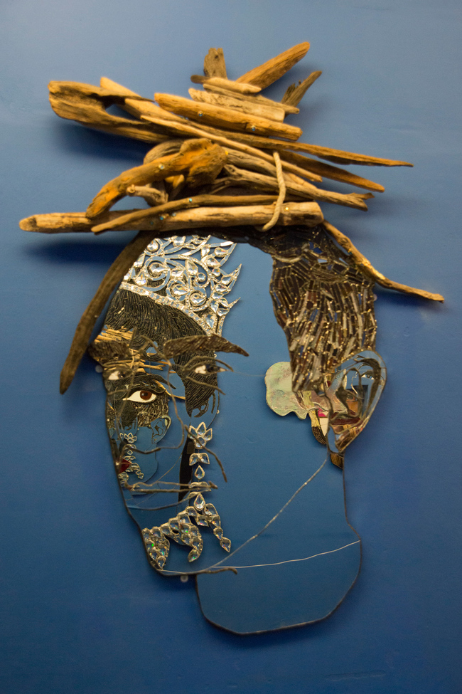 A Collage of materials and spices make a face motif