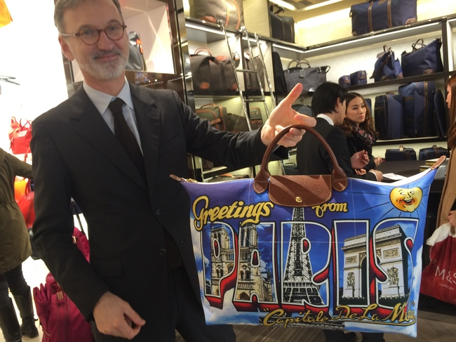 Jean Cassegrain, Longchamp's CEO, holding Jeremy Scott's limited-edition Paris Postcard bag, made especially for the Champs-?lys?es opening