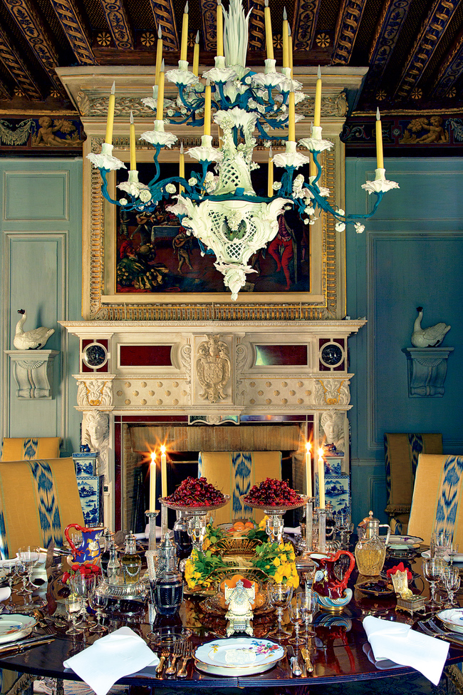 Wideville. A painted t?le and porcelain eighteen-branch composition chandelier, Meissen, 19th century and later, hangs above a table set with a pair of French silver-gilt asparagus dishes and stands, by G. Keller, Paris, late 19th century; pair of cut-glass tazze with Faberg? mark below the imperial warrant, ca. 1885